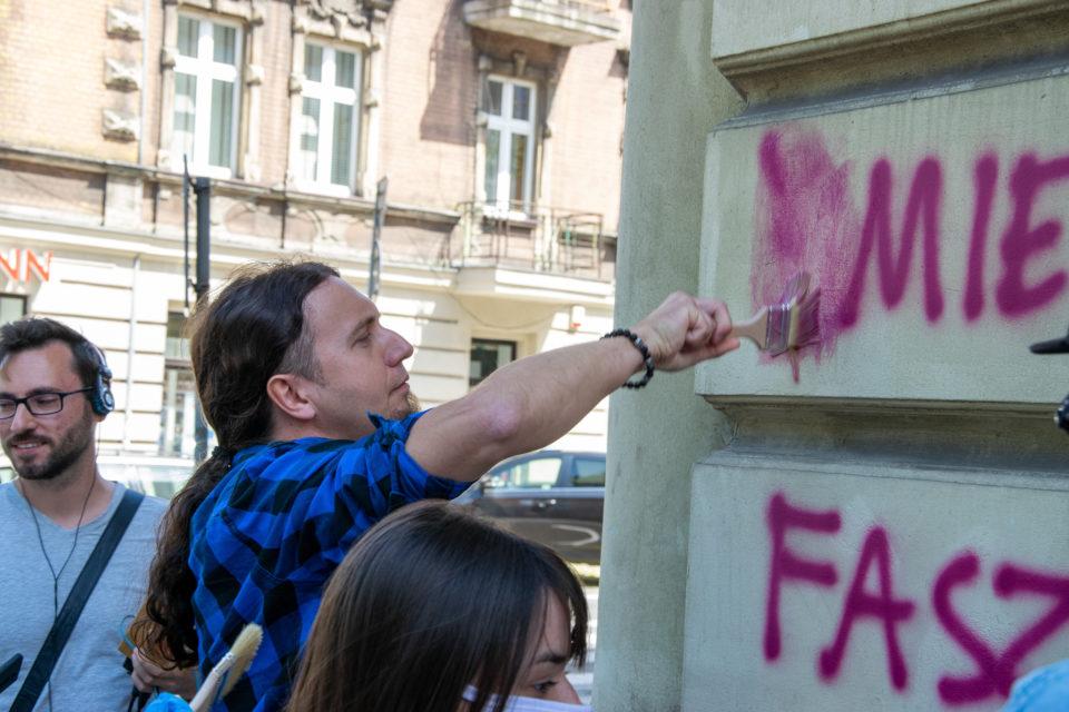 Europoseł Łukasz Kohut zmywa nienawistne graffiti z ulic Katowic.